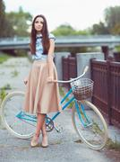 Young beautiful, elegantly dressed woman with bicycle Stock Photos