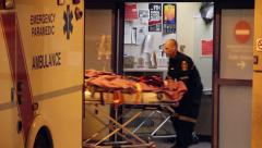 Victim pulled from ambulance into hospital Stock Footage