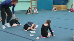 Kids making exercise flexibility on acrobatic lessons on the floor - stock footage