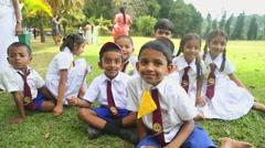 Group of Sri Lankan children in school uniform playing in Botanical Gardens Stock Footage
