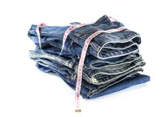 Heap of jeans trousers with tape measure Stock Photos