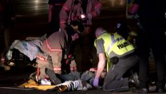 Ambulance staff turning pedestrian accident victim on its back Stock Footage
