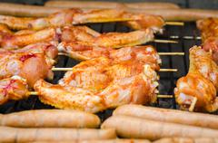 Sausages and chicken wings on smoking grill barbeque Stock Photos