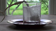 Boiling water for tea with  vintage heating coil tool in glass Stock Footage