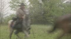 Riders on horseback gallop through fog Stock Footage