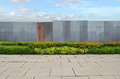 Shrubs with zinc fence on blue sky background Stock Photos
