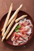 prosciutto ham and grissini bread sticks. italian antipasto - stock photo