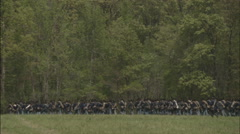 Many soldiers march single file followed by covered wagon - stock footage