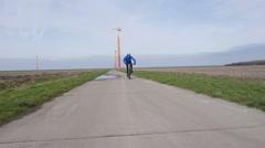 Mountain biker riding near wind turbine Stock Footage
