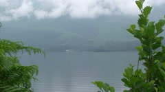 Lake with very still water, mountains, hanging low clouds - stock footage