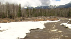 1080HD Cineflex shot following river through trees, past snowy parts - stock footage