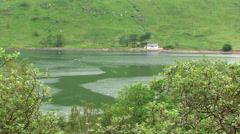 House on the other side of the loch, different water masses Stock Footage