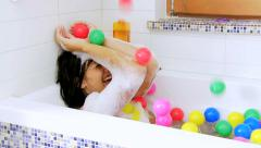 Woman in bath tub with raining colored plastic balls Stock Footage