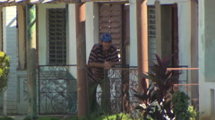 Man on porch of old house, pan up to ripped off roof Stock Footage