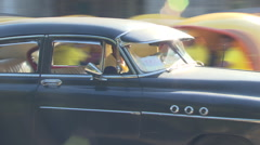 Old American car drives past taxi cabs Stock Footage