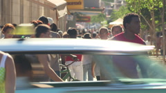 Busy street scene, pedestrians, cars cross in foreground Stock Footage