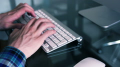 Man typing in a keyboard on a Glasdesk Stock Footage