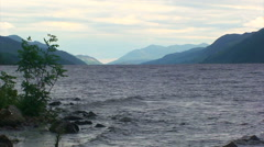View to the South at the long Loch Ness, waves crash on shore Stock Footage