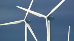 Close up on windmill turbines in front of dark clouds - stock footage