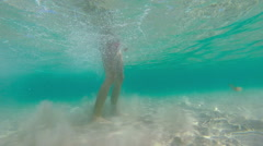 Little girl learning to swim in shallow water in sea. Underwater shot. Stock Footage