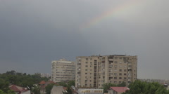 Beautiful rainbow over tall apartments flat, green trees and houses view below Stock Footage