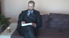 Businessman with pen and clipboard working relaxed on sofa, at home, nice view Stock Footage