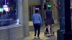4K UHD pedestrians approach crosswalk wearing lit up head wear holiday ladies Stock Footage