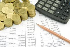 Coin on finance account with pencil and calculator Stock Photos