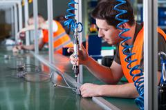 Men during precision work on production line Stock Photos