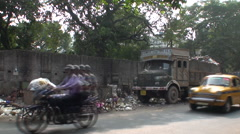 Traffic drives down a busy and dirty street in Calcutta Stock Footage