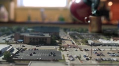 A huge cup of tea gets poured over a miniature tilt shift city. - stock footage