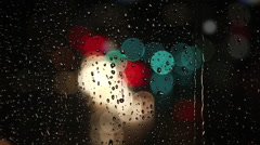 Rain drops on window with traffic bokeh Stock Footage