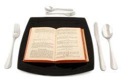Metaphoric concept with physics book in the plate with cutlery Stock Photos