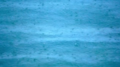 Rain drops falling on sea surface nice blue color. Video Stock Footage