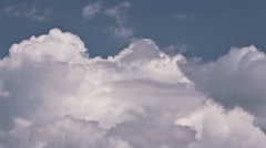 Fluffy cumulus clouds against light blue sky - time lapsed Stock Footage