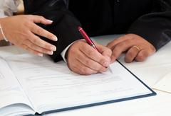 Stock Photo of bride and groom signing marriage certificate