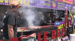 Stock Video Footage of BBQ Ribfest event on a warm sunny summer day with ribs cooking.