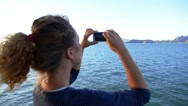 Stock Video Footage of Slow Motion of Woman Taking Photograph with a Smart Phone Camera of Seascape