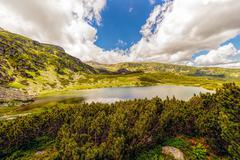 Landscape with a glacial lake in the highlands of fagaras mountains, romania Stock Photos
