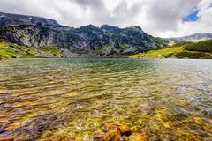 Landscape with a glacial lake in the highlands of fagaras mountains, romania Stock Photos
