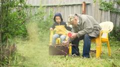 Pojanpoika ja isoisä istuu tulen pihalla Arkistovideo