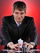 Handsome poker player with two aces in his hands Stock Photos