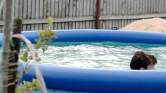 Boy swimming in inflatable pool in the yard Stock Footage