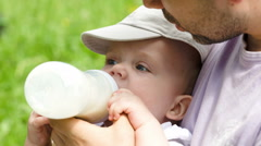 Dad feeding his baby from the bottle outdoor Stock Footage