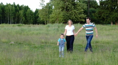 Mother, father and son walking on the meadow - stock footage
