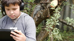 Boy with headphones and touchpad outdoor - stock footage