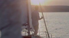 Young man stands on a yacht in the morning looking into the distance 2 - stock footage