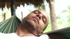 Man relaxing in a swinging hammock - stock footage