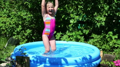 cheerful girl in inflatable pool in summer garden - stock footage