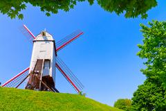 Windmill and green lawn at Brugge - stock photo